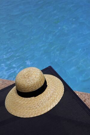 Straw hat and bath mat by the pool