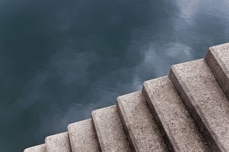 Close up of concrete stairs leading down to a lake