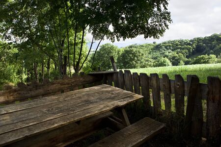 Terrace with wooden table and bench in a French countryside