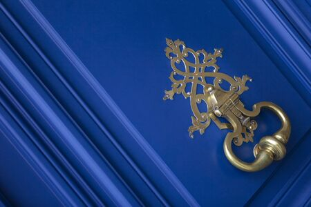 Stylish copper knocker on a French mansion blue wooden door