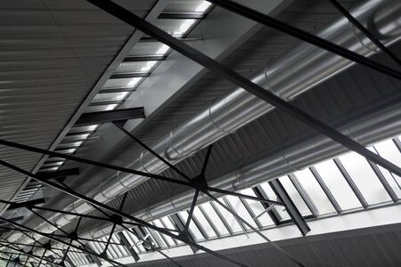 Ceiling of a factory with metal beams and evacuation ducts