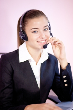 Stylish attractive receptionist or call centre operator wearing a headset seated at her desk looking at the camera with a smile Stock Photo - 16013810