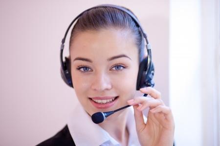 Primer plano retrato de una cabeza recepcionista atractivo o asistente personal que llevaba un auricular y micrófono de contestar una llamada