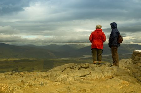 glen: two walkers looking across scenic landscape