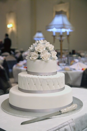 A white wedding cake with white icing roses photo