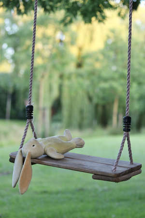 Abandoned stuffed bunny on swing with blurred background, concept for lost or missing child