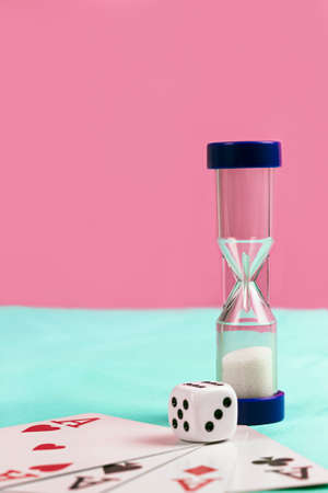 sand timer: Playing Cards with Blue Sand Timer and Die on Blue and Pink Background Stock Photo