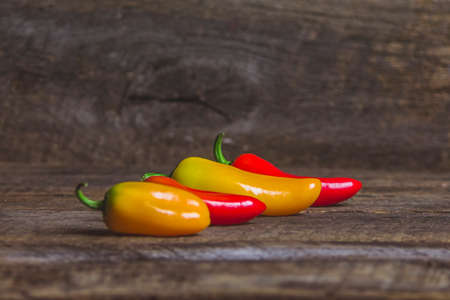 raw food: Four Yellow and Red Vegetable Peppers on Wood Background Stock Photo