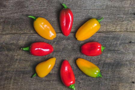 alimentos y bebidas: Pimientos vegetales amarillos y rojos en el fondo de madera