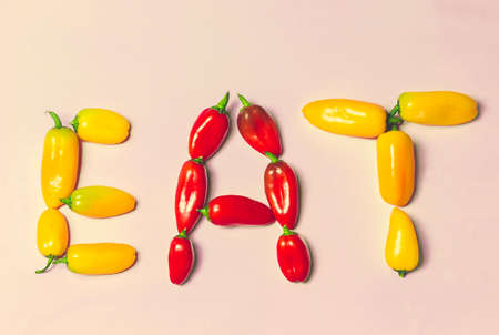 sweet peppers: EAT Typography Text With Yellow and Red Sweet Peppers on Pink Background