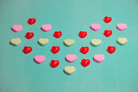 conversational: Valentines Day Red Gummy and  Conversation Hearts on Green Background