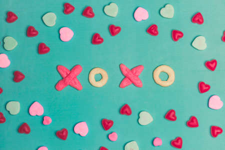 xoxo: Valentines Day XOXO Typography Cookies And Conversation Hearts on Green Background