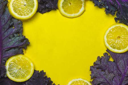 Lemon and Kale Frame on Yellow Background Stock Photo