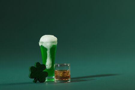 St. Patrick's Pint of Beer and Scotch Whiskey with Wood Four Leaf Clover on a Green Background
