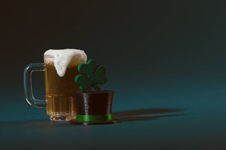 Mug of Beer, Leprechaun Hat and Four Leaf Clovers on a Green Background