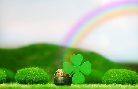 St. Patrick's Day Themed Pot of Gold with Four-Leaf Clover Under Colorful Rainbow on a Clear Day