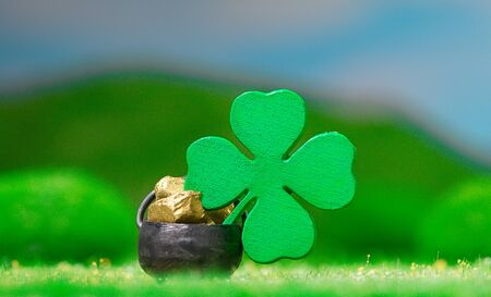 St. Patrick's Day Themed Pot of Gold with Four-Leaf Clover on grassy meadow