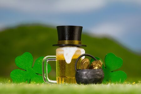 Mug of amber-colored beer, four-leaf clovers  and a pot of gold on a grassy outdoor meadow