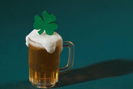 Mug of Beer and Green Wood Four-Leaf Clover Stock Photo