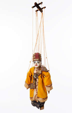 Suspended by wires ancient Asian wooden marionette representing a man. Dressed in traditional clothes. Studio photo, white background.