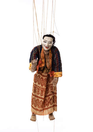 Suspended by wires ancient Asian wooden marionette representing women. She is dressed in traditional clothes. Studio photo, white background.
