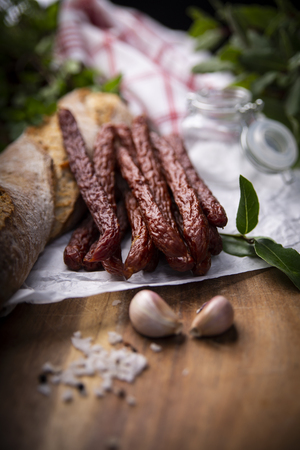 Smoked sausage, a composition of traditional dry, thin rural meats on a dark background. Regional food.