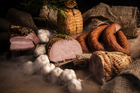 Traditionally smoked, homely sausage in composition with fresh garlic and herbs. Horizontal composition. Reklamní fotografie