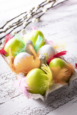 Easter composition, colorful eggs and willow branches on a wooden background. 写真素材