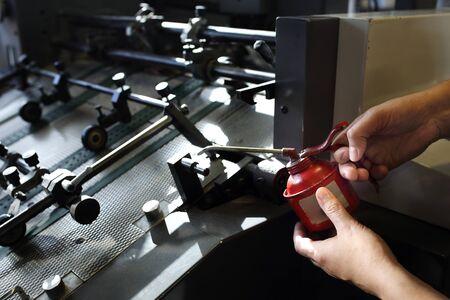 The mechanic maintains the printing machine.