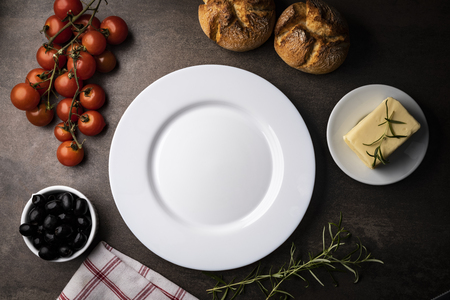 White empty plate, meal meal, yellow cheese, butter and fresh bread rolls on a dark table. Horizontal frame, top view.
