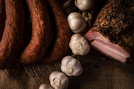 Traditionally smoked, homely sausage in a composition with fresh garlic, horizontal composition.