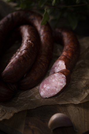 A bunch of dry, smoked sausage on an ecological rural natural background. Banco de Imagens
