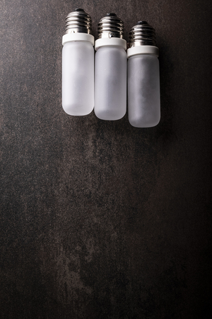 Composition of light bulbs on a dark background, vertical composition with space for text.