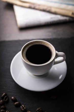 A cup of aromatic black coffee on a wood table.