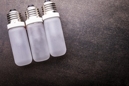 Composition of light bulbs on a dark background, horizontal composition with space for text.