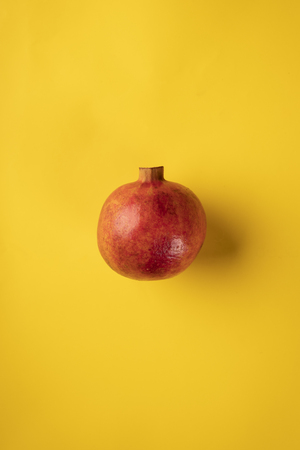 One pomegranate fruit isolated on a yellow background Stock Photo