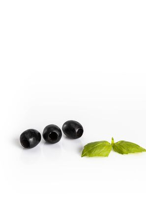 Black olives in a bowl on a white background. culinary composition Фото со стока