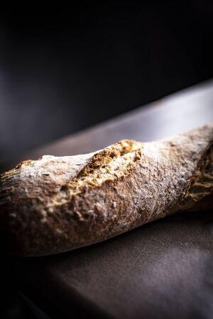 Bread on a black background. fresh wheat bread roll