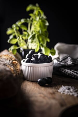 A composition of black olives, olive oil and bread on a kitchen counter top Фото со стока