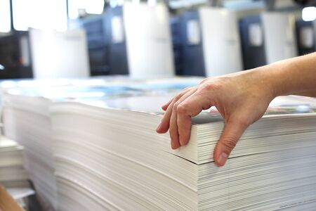 Work in the printing house, the employee checks the paper's weight. Stock Photo