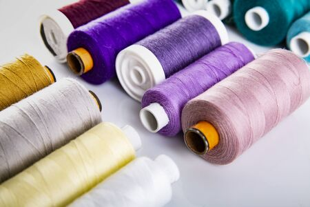 Colorful cotton thread bobbins on a white background.