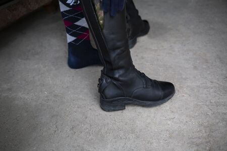 Stud, woman puts on professional leather riding boots. 写真素材