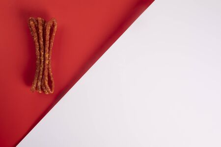Smoked sausage, a composition of traditional dry, thin rural meats on a red background. Regional food. Stockfoto