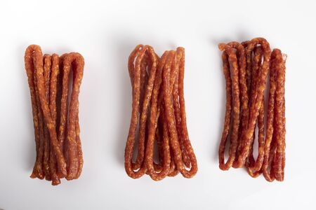 Smoked sausage, a composition of traditional dry, thin rural meats on a white background. Regional food.