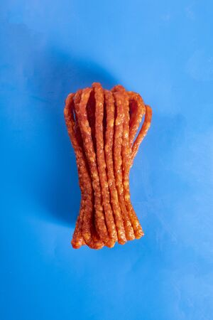 Smoked sausage, a composition of traditional dry, thin rural meats on a blue background. Regional food.