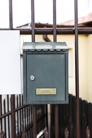 A metal letterbox mounted on the entrance gate to the house