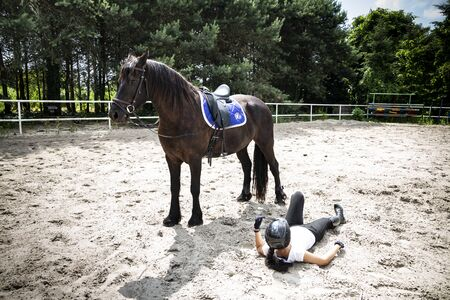 The woman rider fell off his horse.