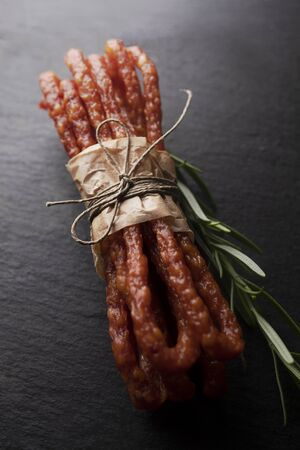 Smoked sausage, a composition of traditional dry, thin rural meats on background. Regional food.