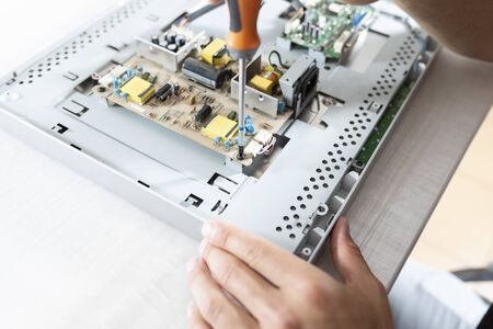 Computer repair in a professional service. A man with a screwdriver screwed screws Stock Photo