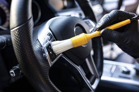 De man stofzuigt de interieurdetails van de auto met een borstel